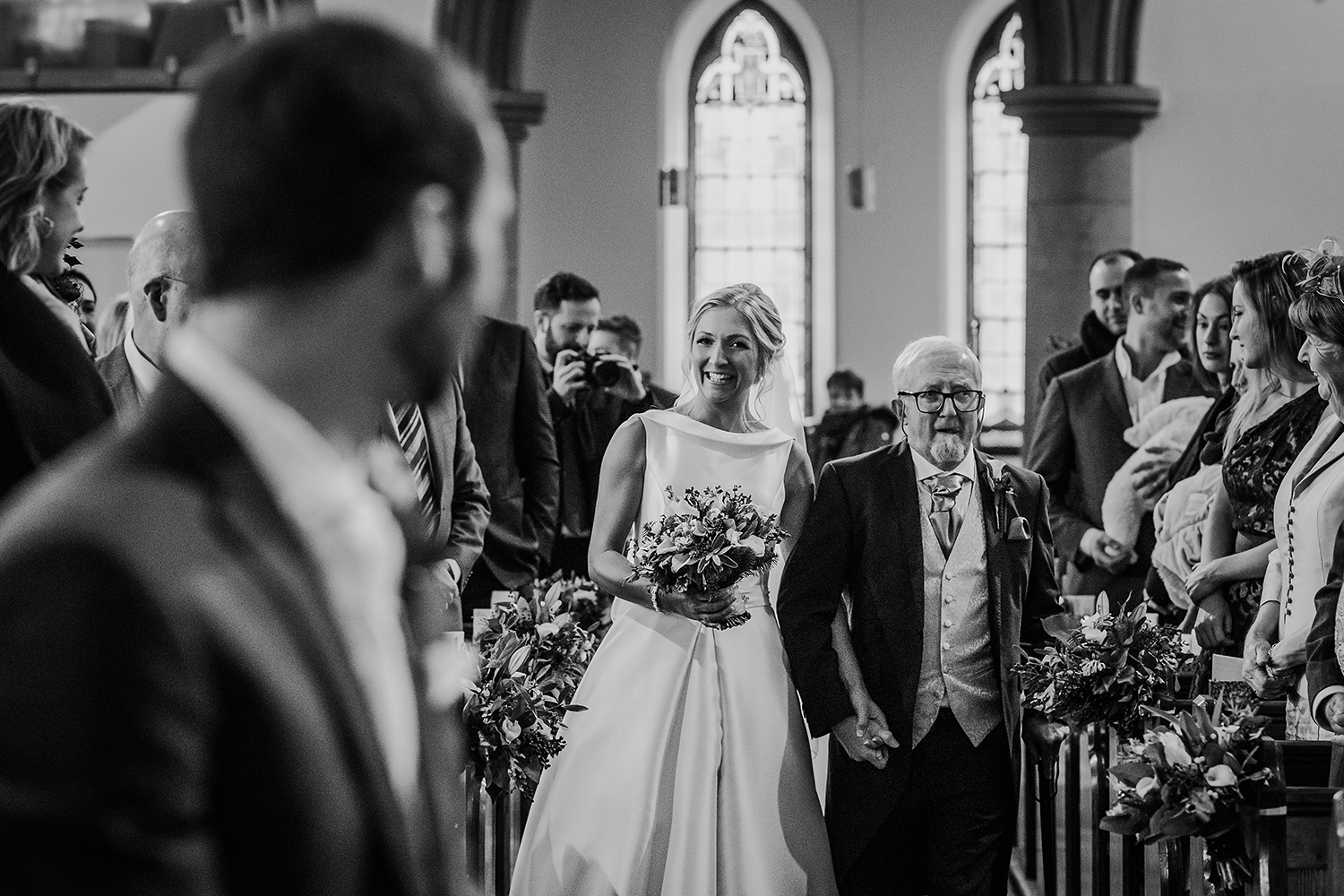 bride smiles at groom as she walks down the aisle with her father. Black and white photo