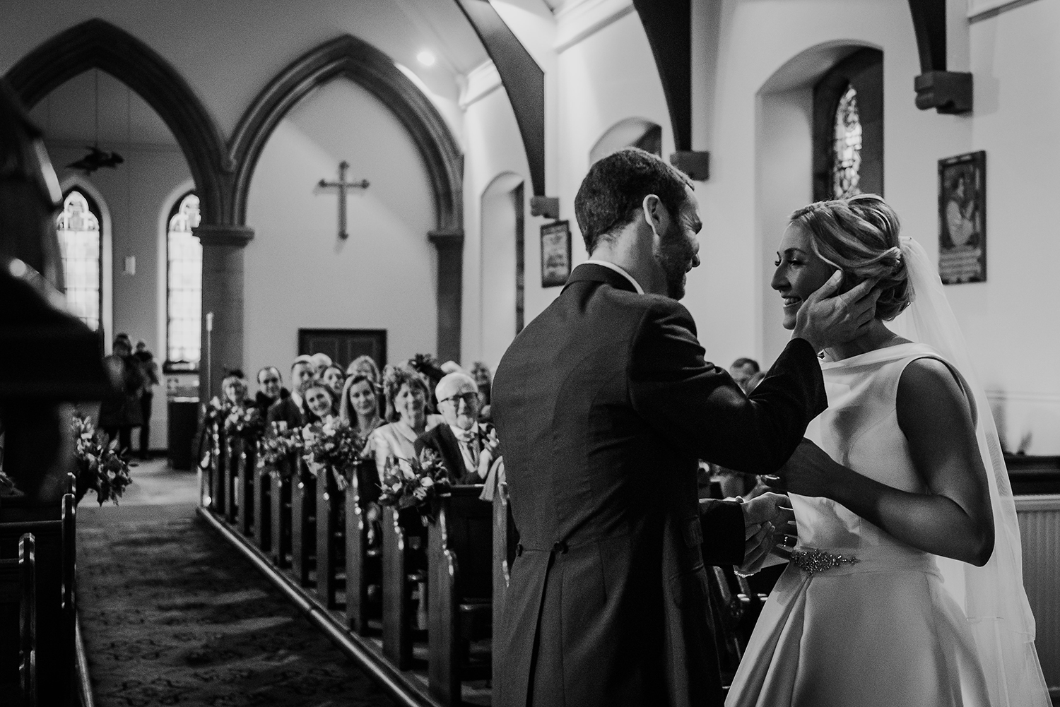 Black and white photo of the grooms hand on the brides face about to kiss