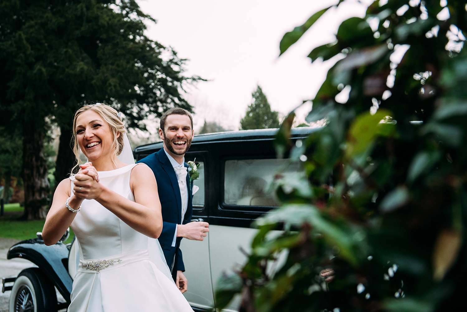 Bride and groom looking happy as they arrive at Mitton hall and see their favourite planner is running the day