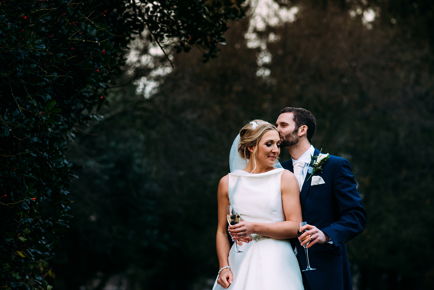 Groom kisses bride at Mitton hall