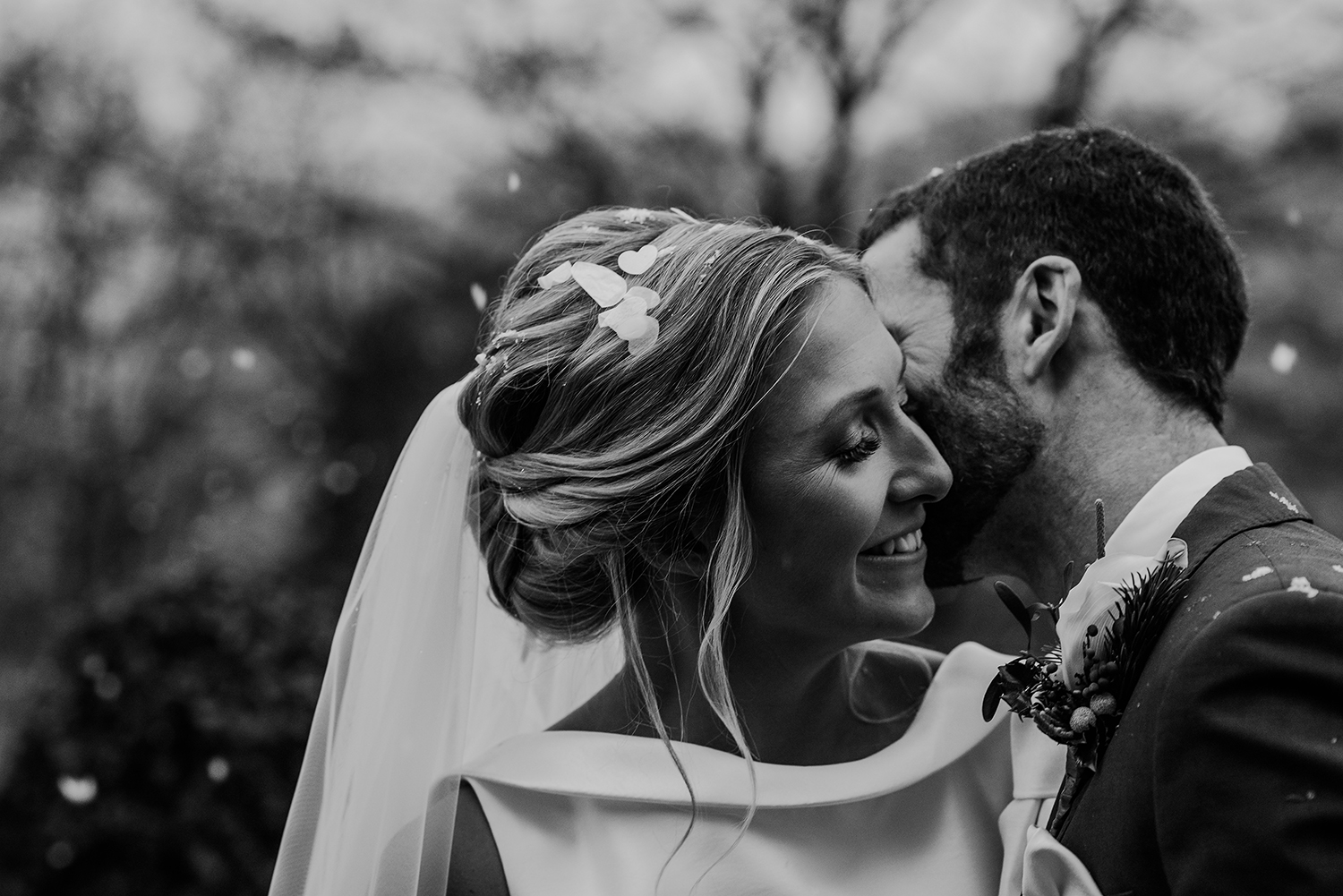 Black and white photo of the groom kissing the bride in the snow