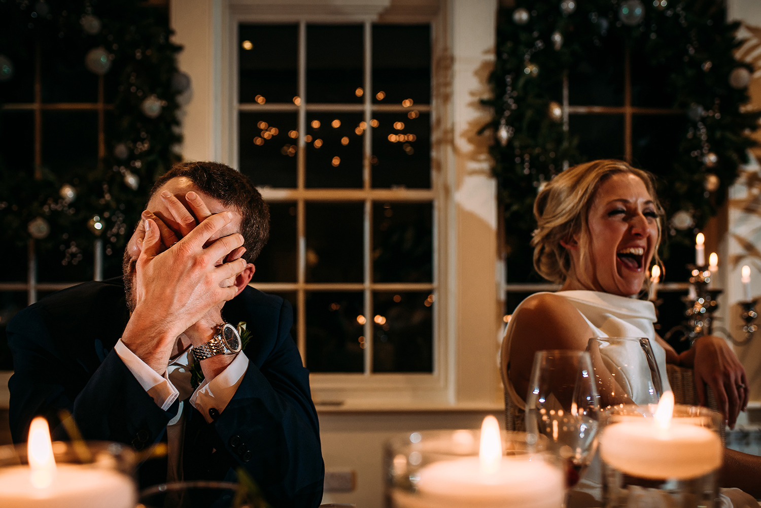 Groom head in hands, bride to his side laughing