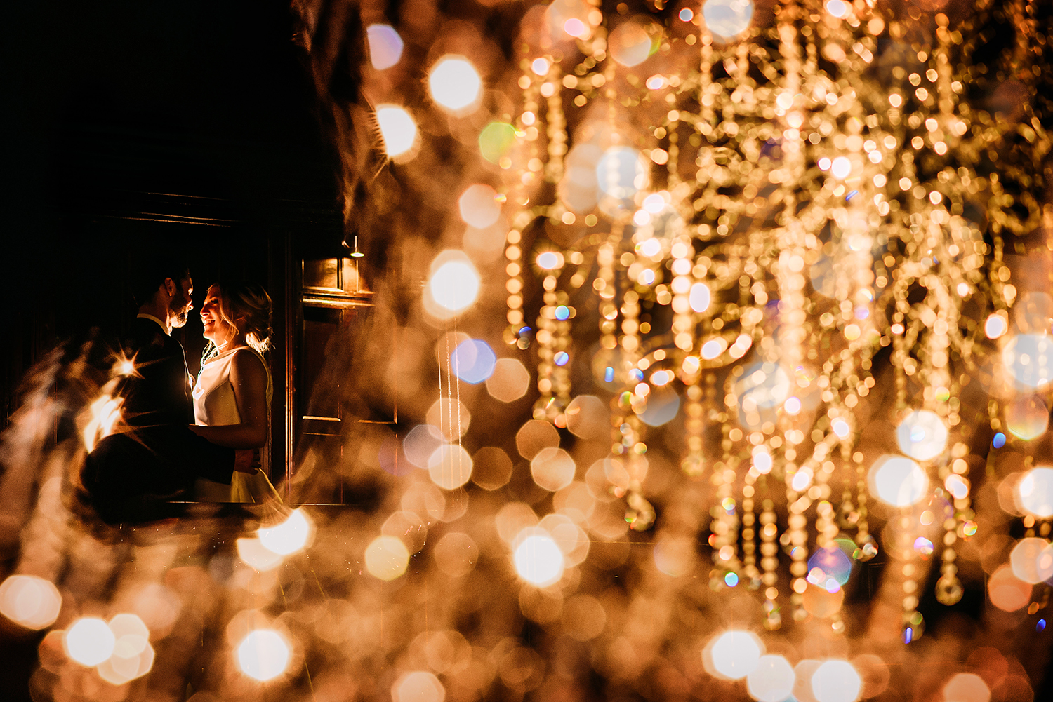 bride and groom flash photo shot through Mitton halls huge chandelier