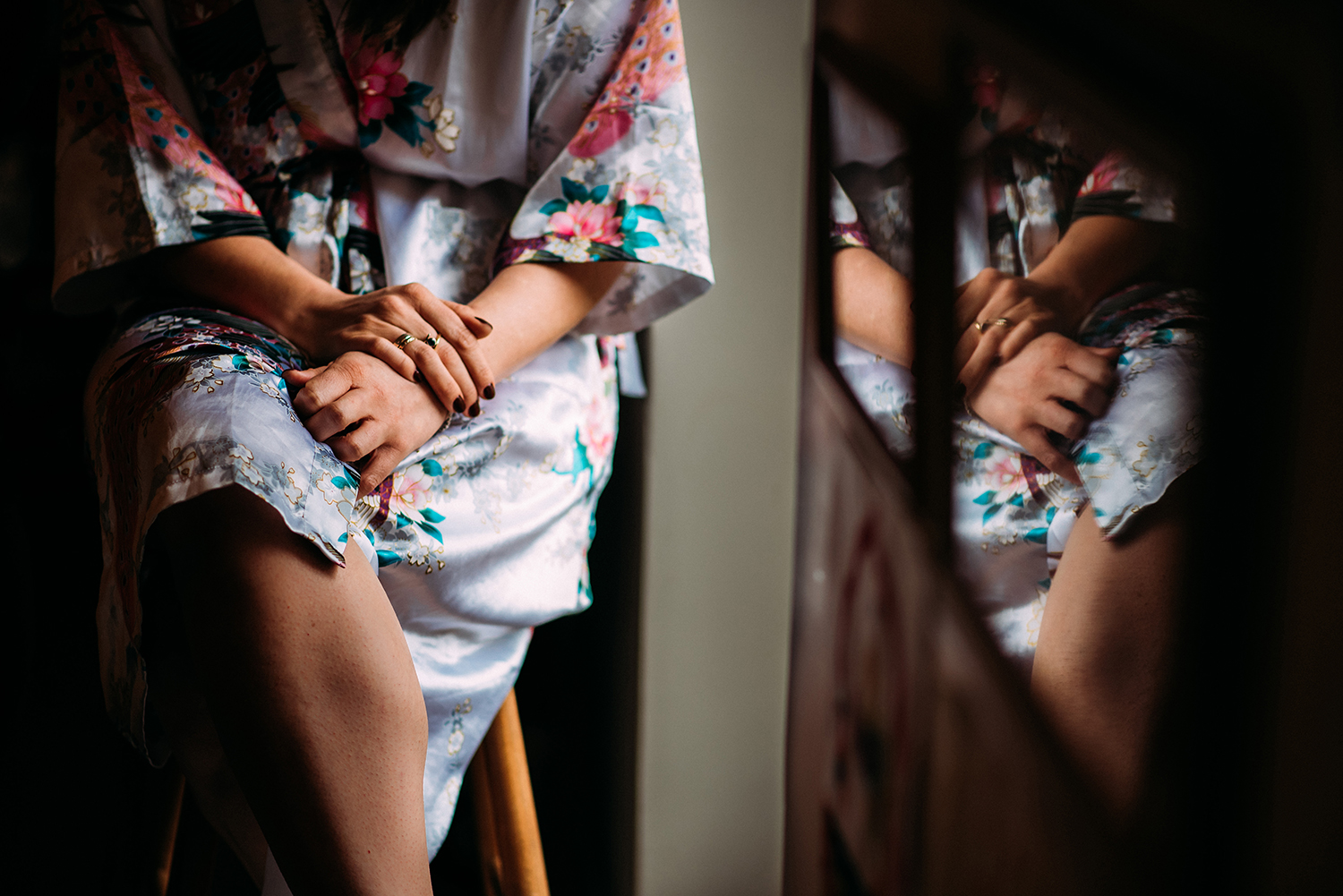 brides hands on lap with reflection in frames
