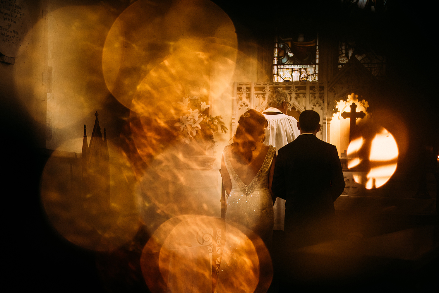 Bokeh shot of bride and groom at the alter though Christmas tree lights
