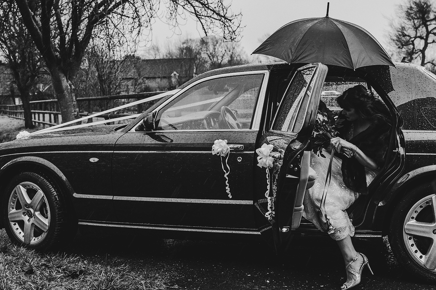 BW photo of the bride getting into the car under an umbrella