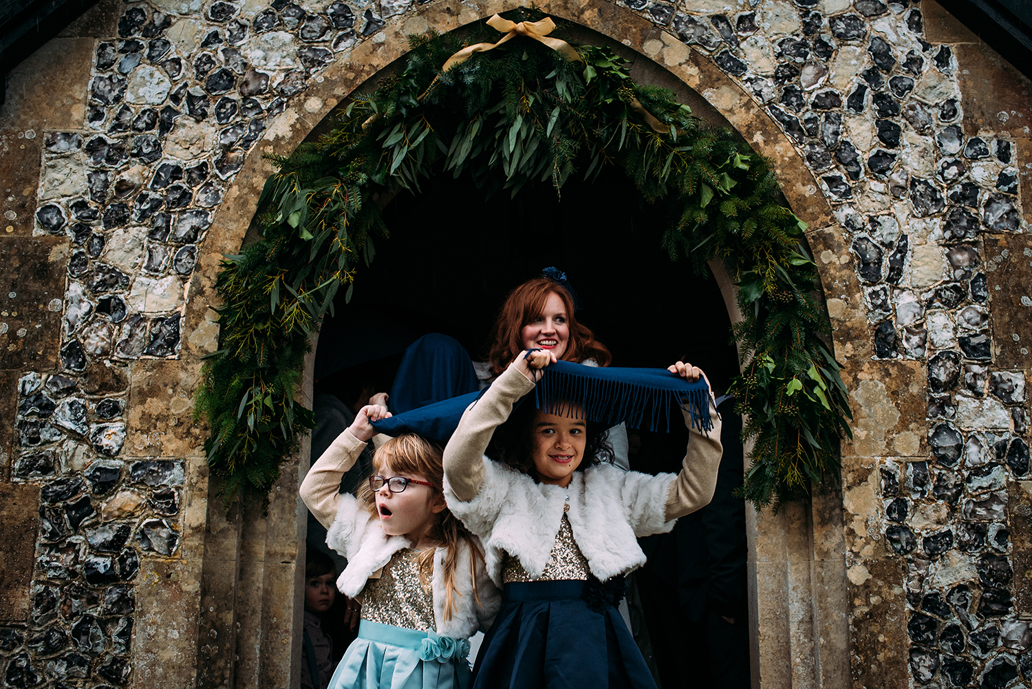 Girls running out from church under cover