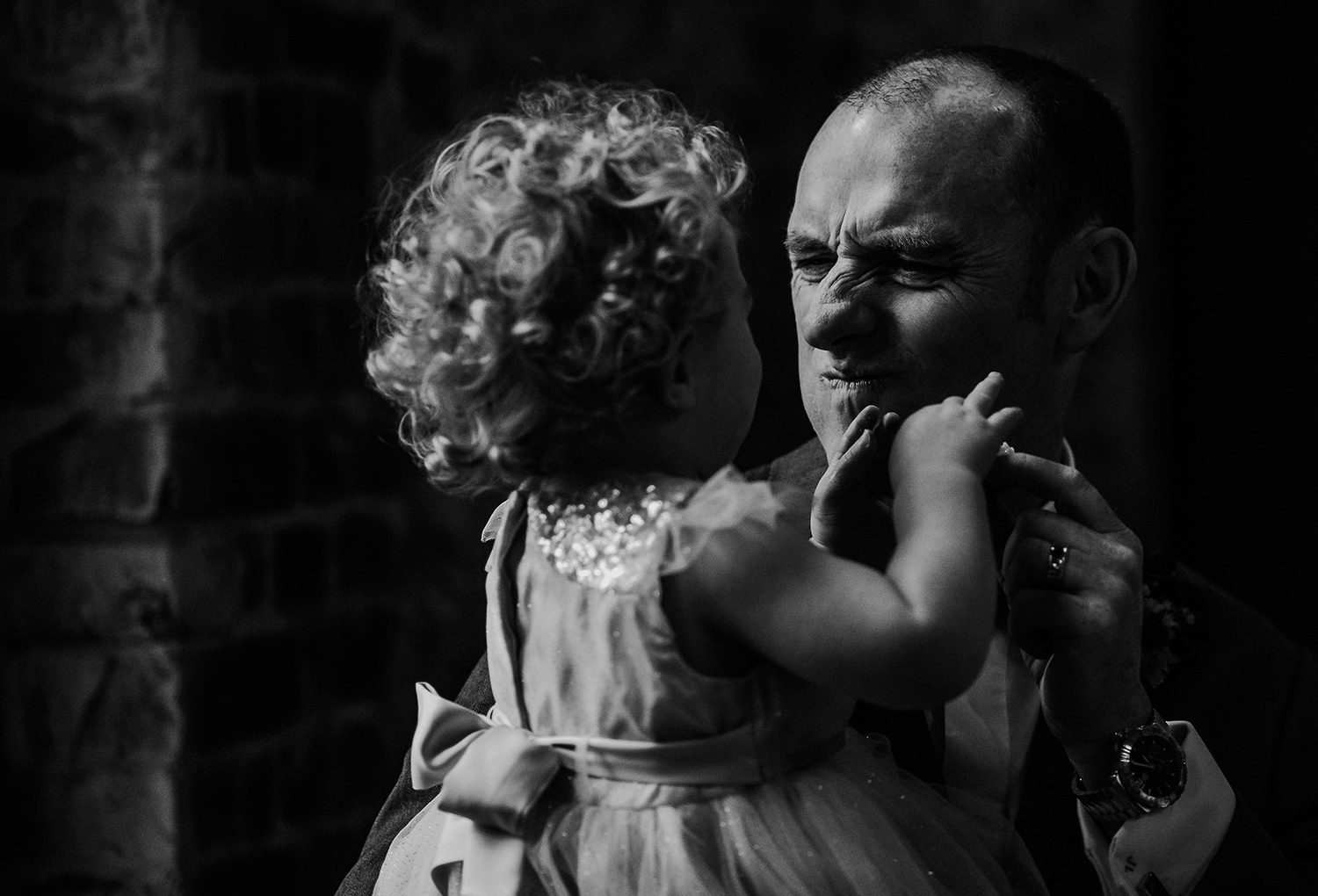 groom pulling faces at his daughter. BW photo