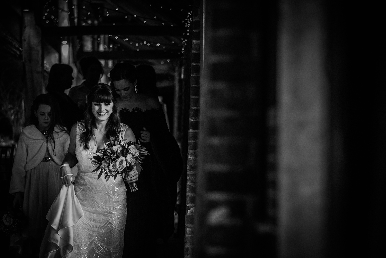 BW photo of bride walking past a window
