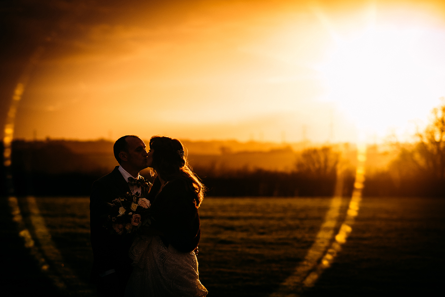 Bride and groom kissing at sunset with big lens flare