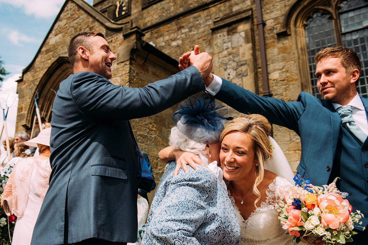 Bride hugs grandma and groom 'high-five's' his friend over the top