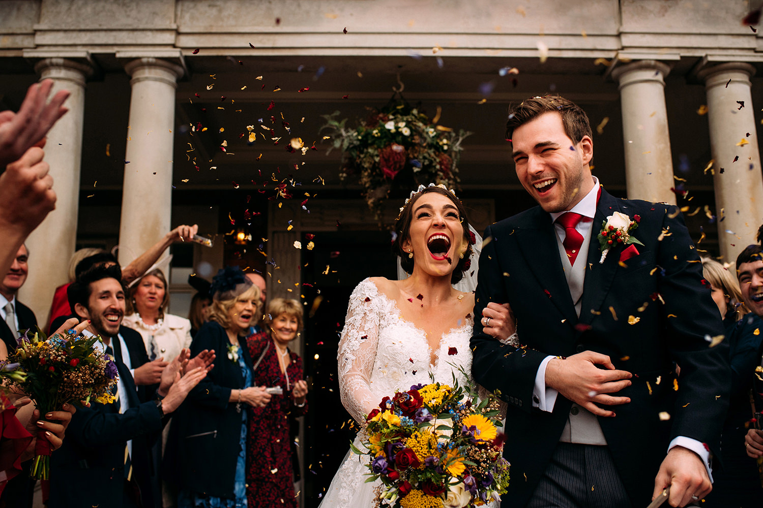 Bride and groom with happy faces walking through confetti out of Eaves hall