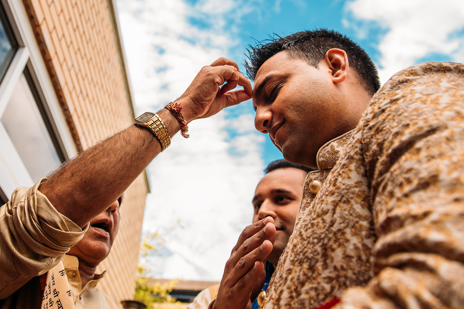 Groom having rice put on his forehead during his entrance