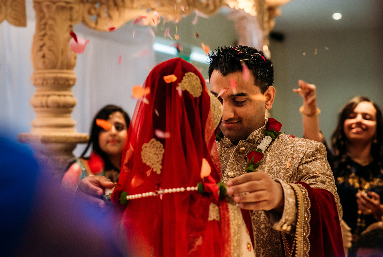 groom putting a necklace on the bride while confetti is thrown at them