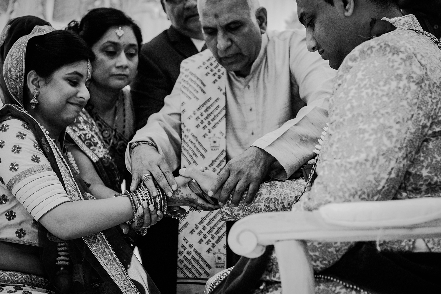 bw photo of the priest joining the bride and grooms hands