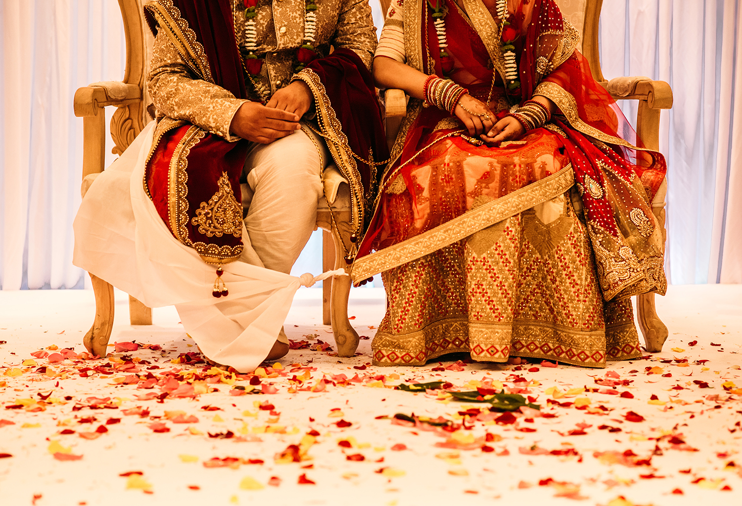 bride and groom from the waist down sat in ceremony chairs with traditional clothes. The floor covered in flower petals