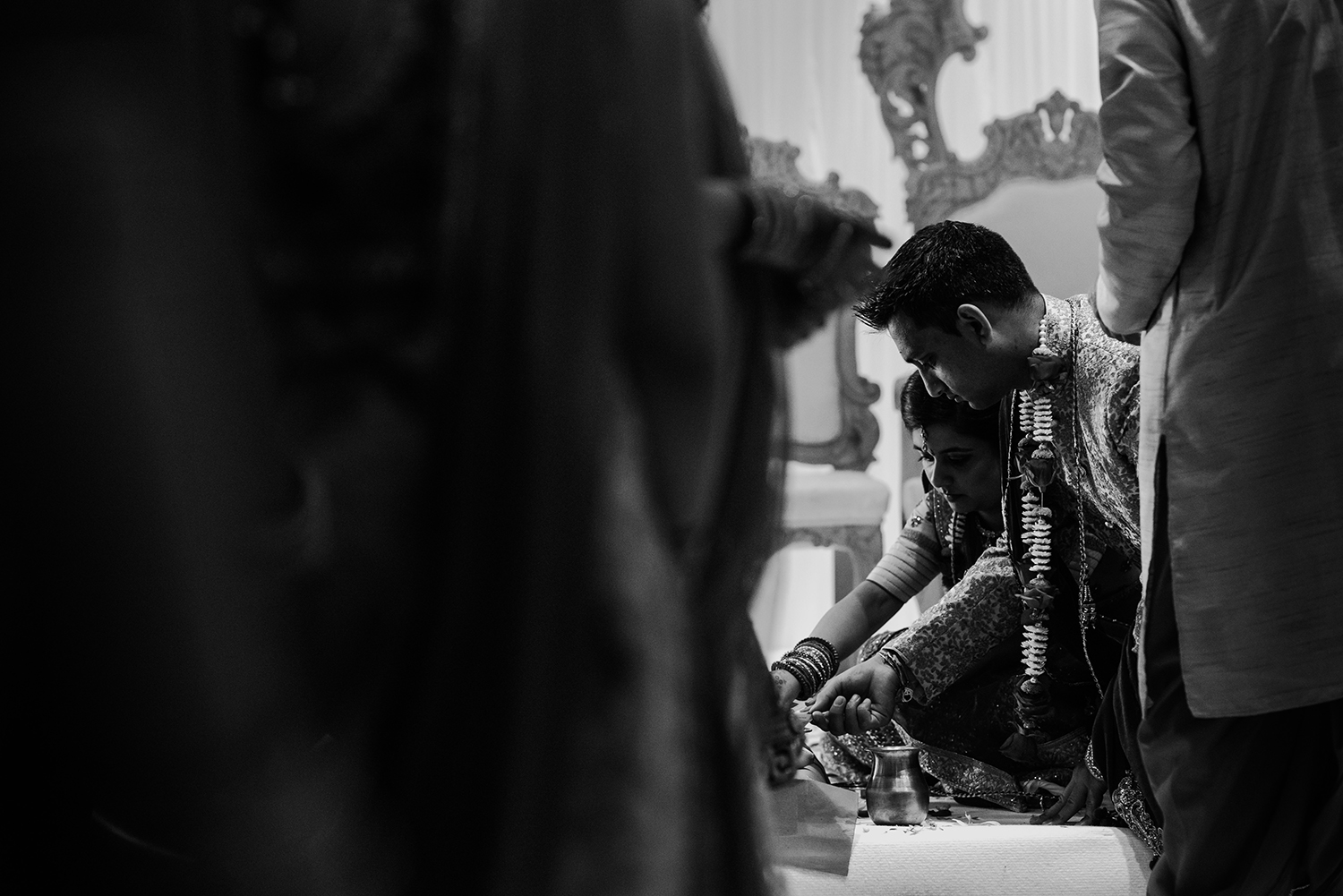 bw photo of bride and groom kneeling and praying
