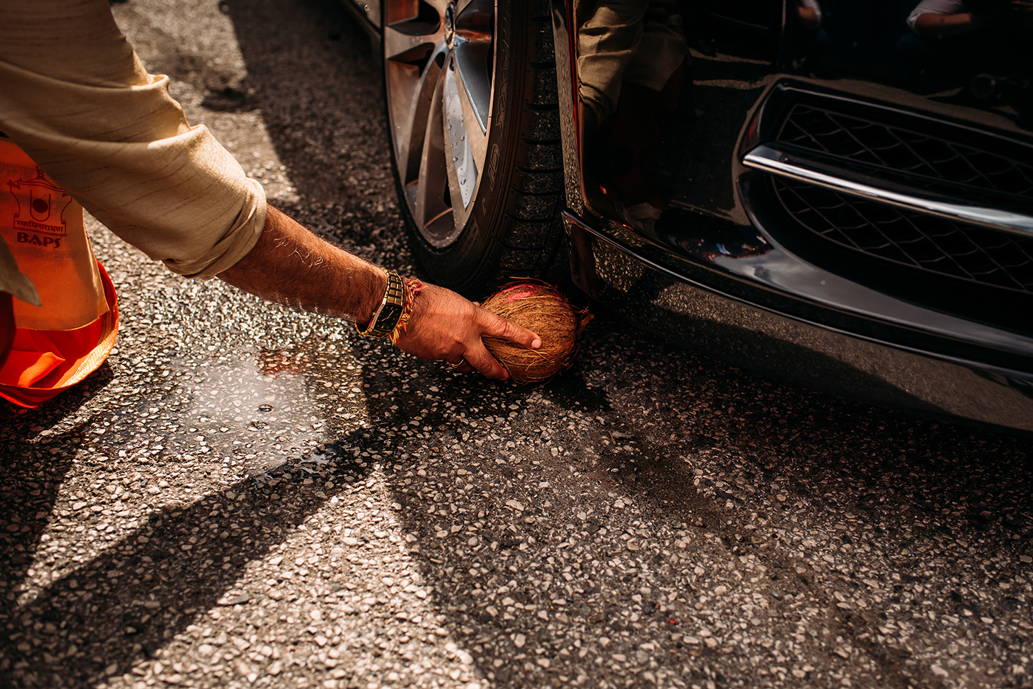 a coconut being placed under the car tyre