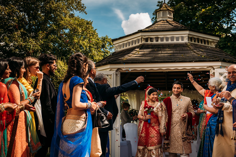 bride and groom leave under confetti