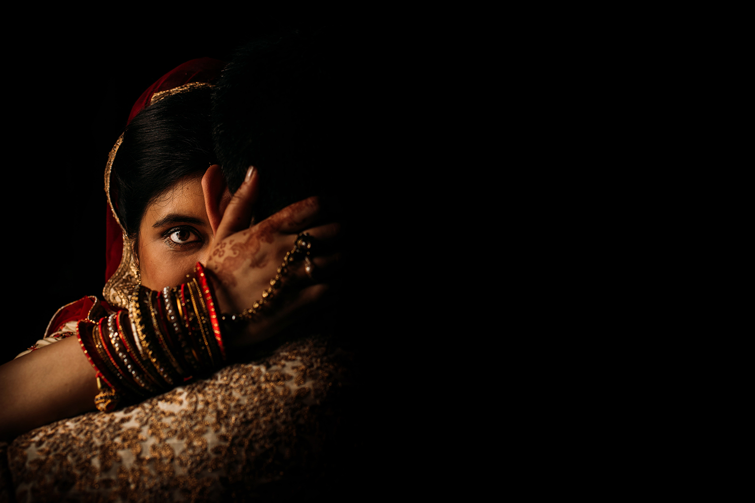 posed shot of bride staring into the camera with traditional Indian hand details and stunning light