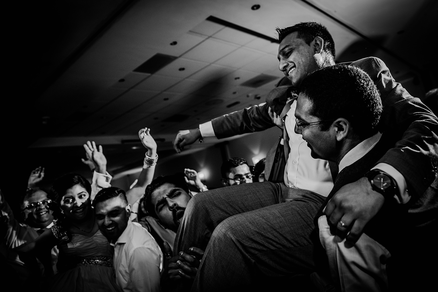 bw photo of bride and groom being lifted on the dancefloor