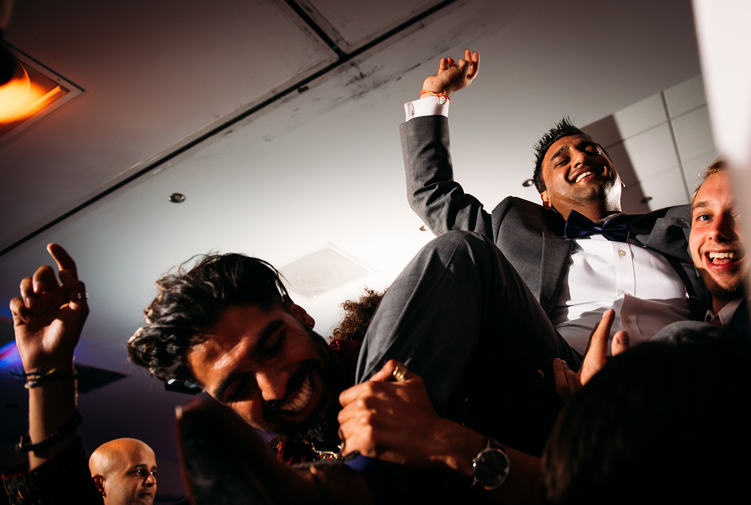 action photo of groom being lifted on the dancefloor