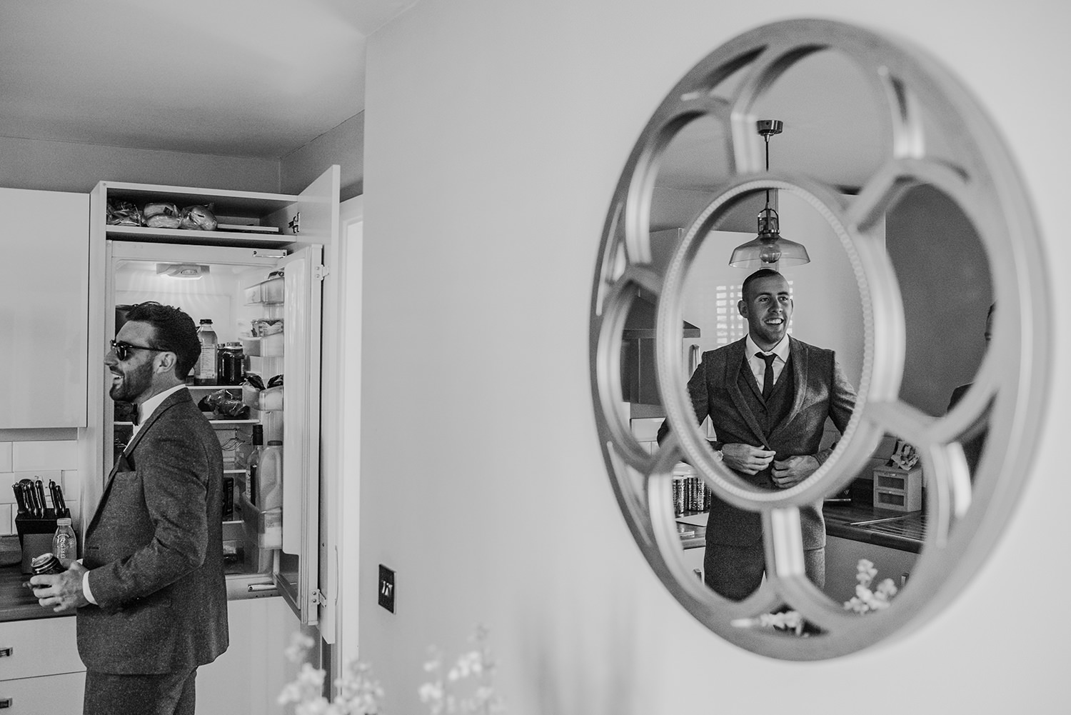bw photo with the groom laughing as he gets a beer out of the fridge and a reflection of his best man laughing back at him.