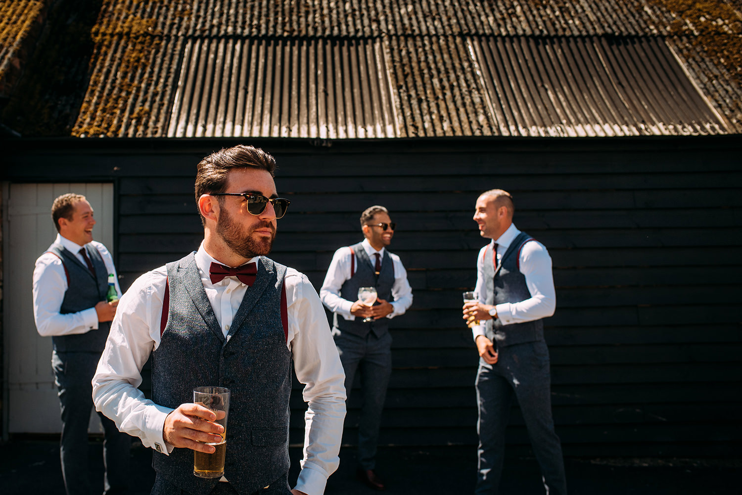 cool shot of the groom and his men by a shed in strong light