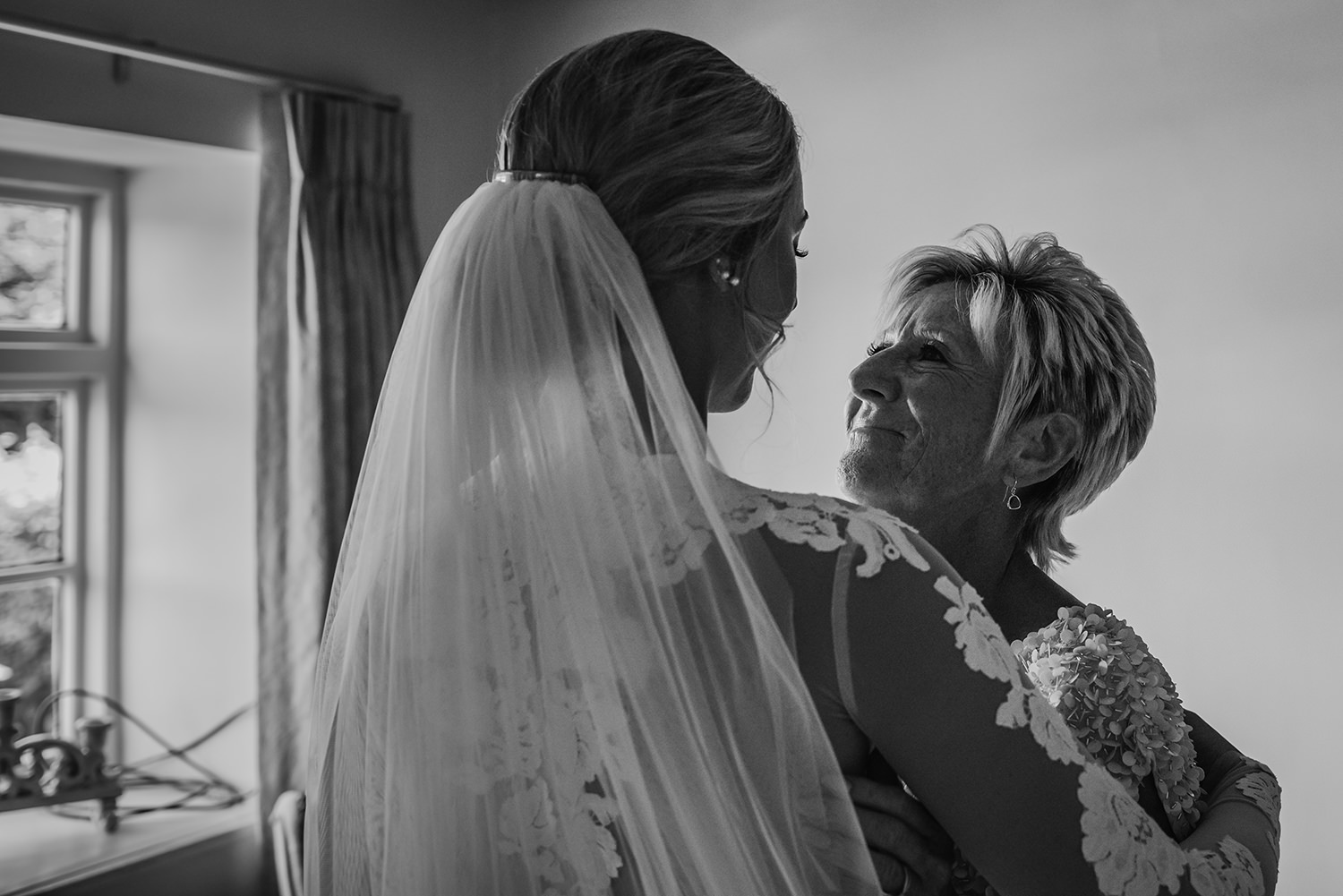 bw photo of bride's mum hugging bride and looking proud