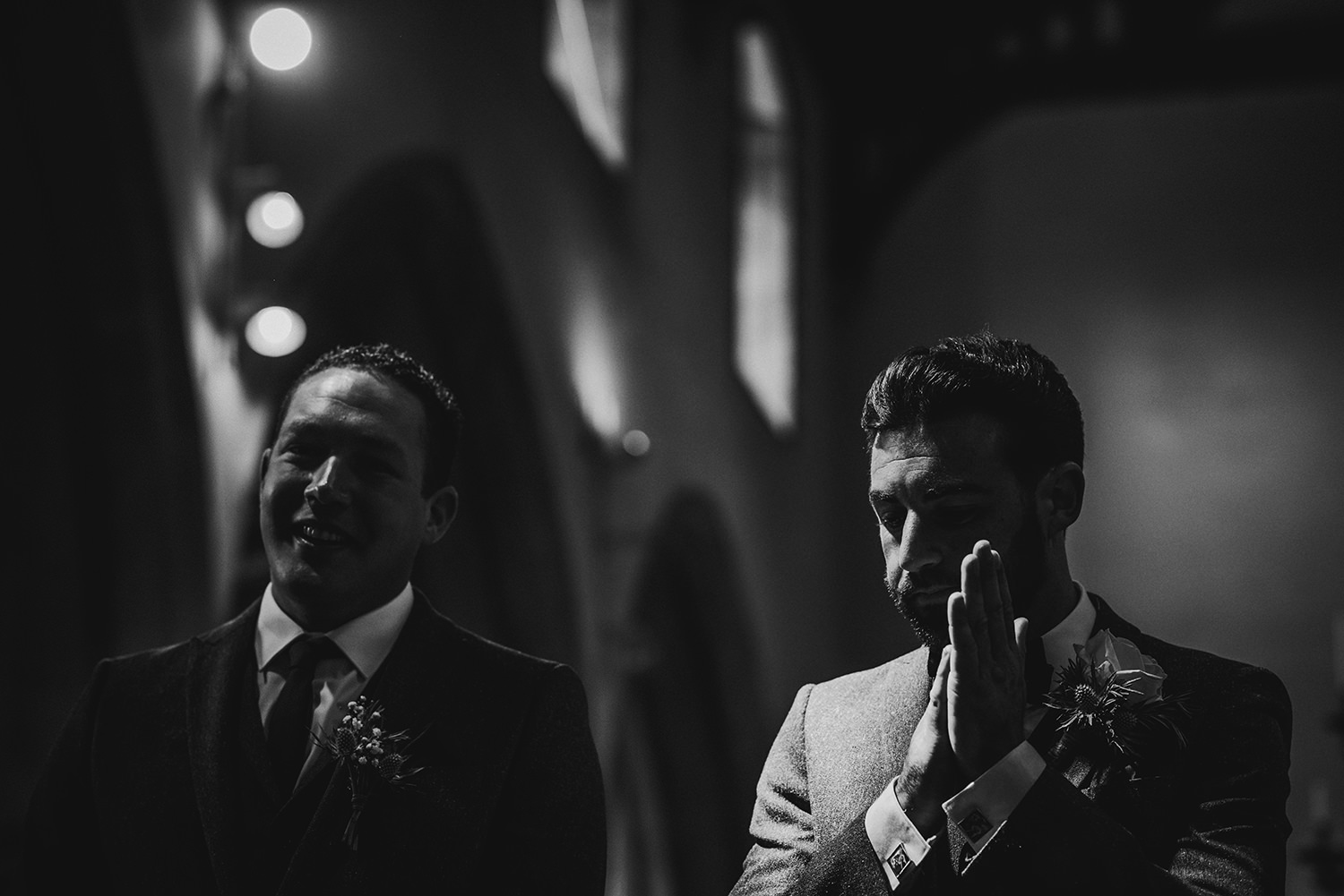 bw photo. Groom rubs hands nervously in strong light