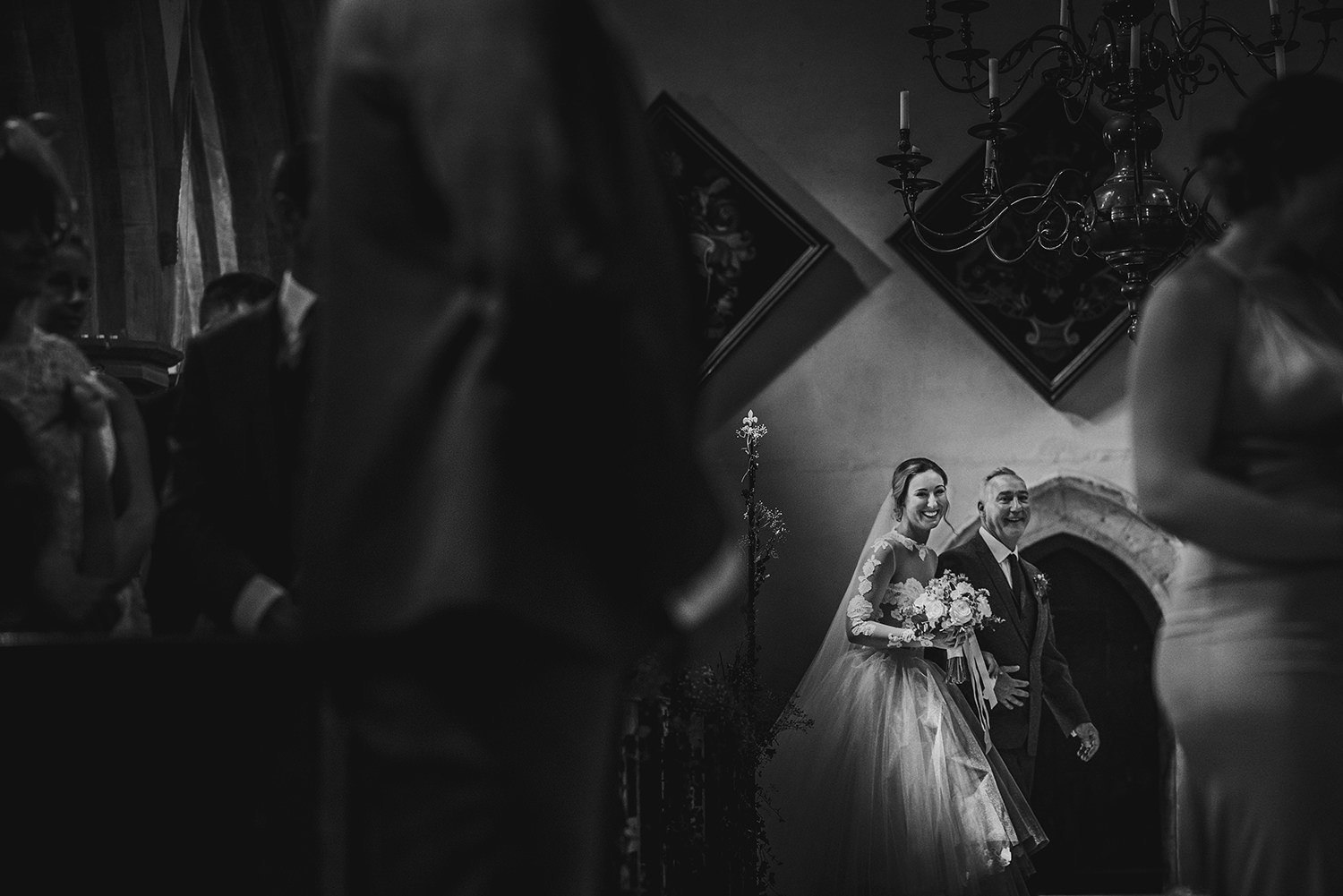 BW photo of the bride entering with her father
