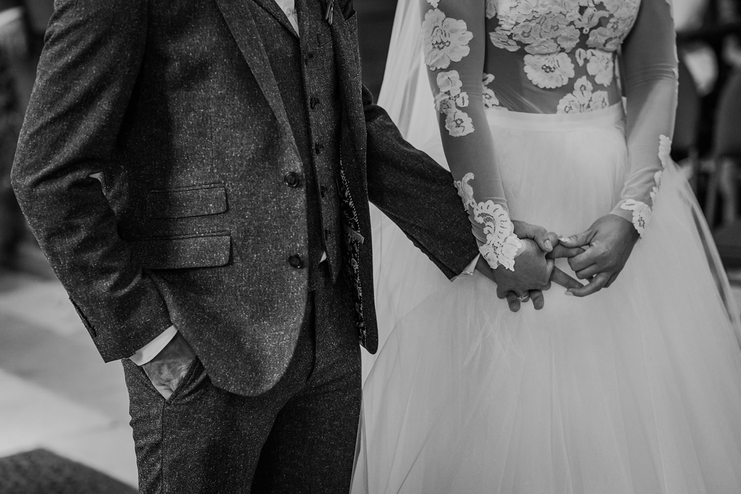 bw photo of bride and groom holding hands
