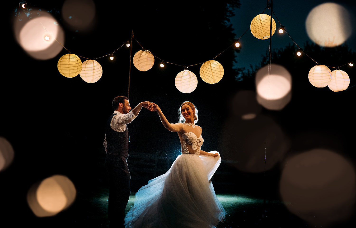night time image of the bride and groom dancing under lanterns