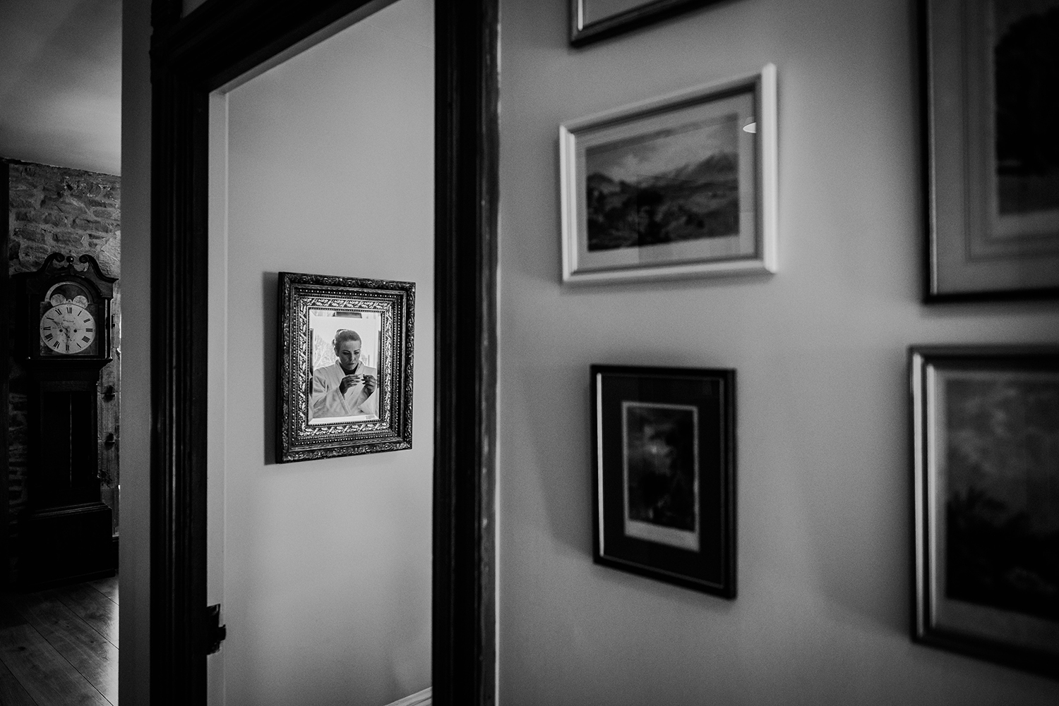 multiple frames on the wall, one has a reflection of a bridesmaid.