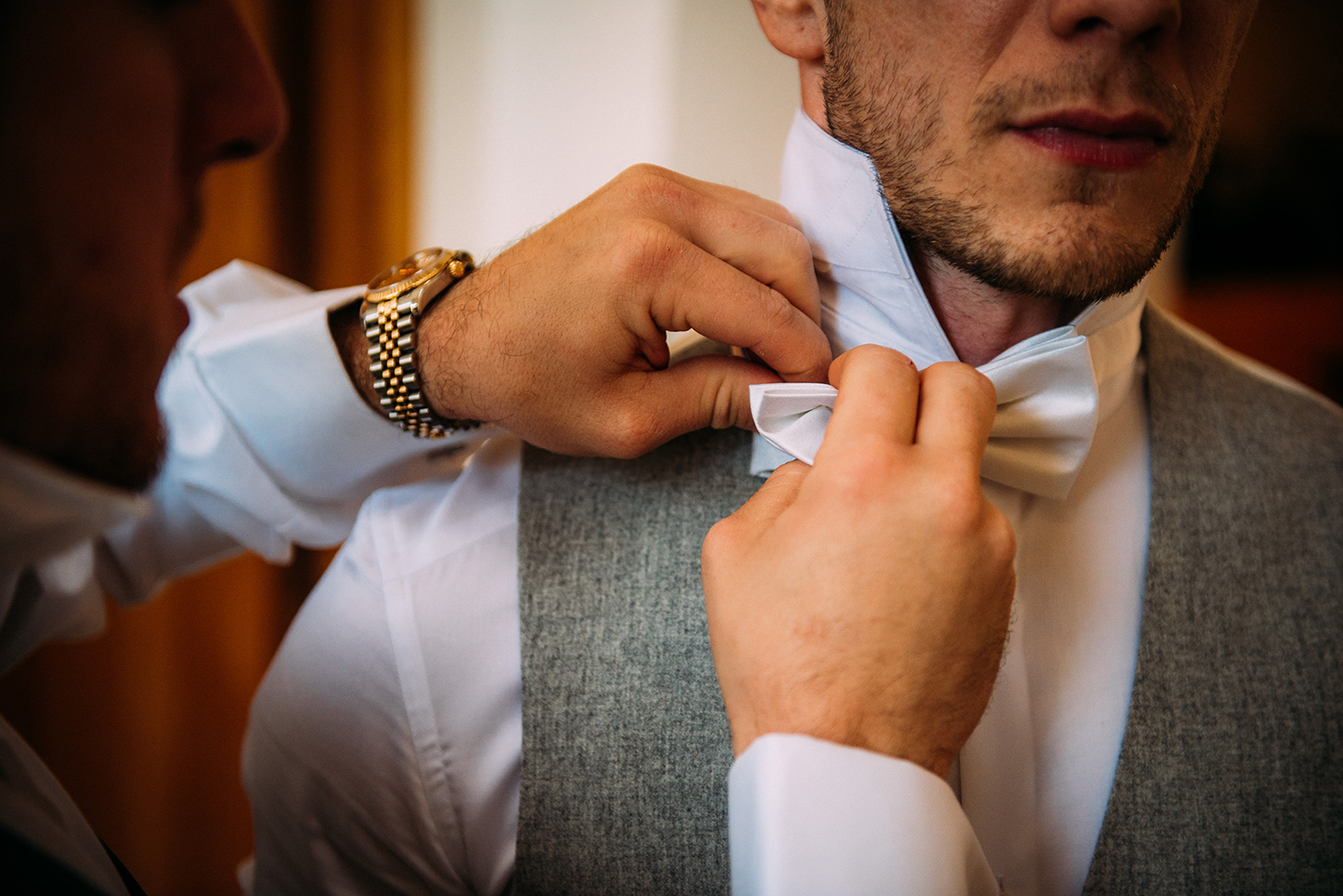 close up of groom's bow tie being done