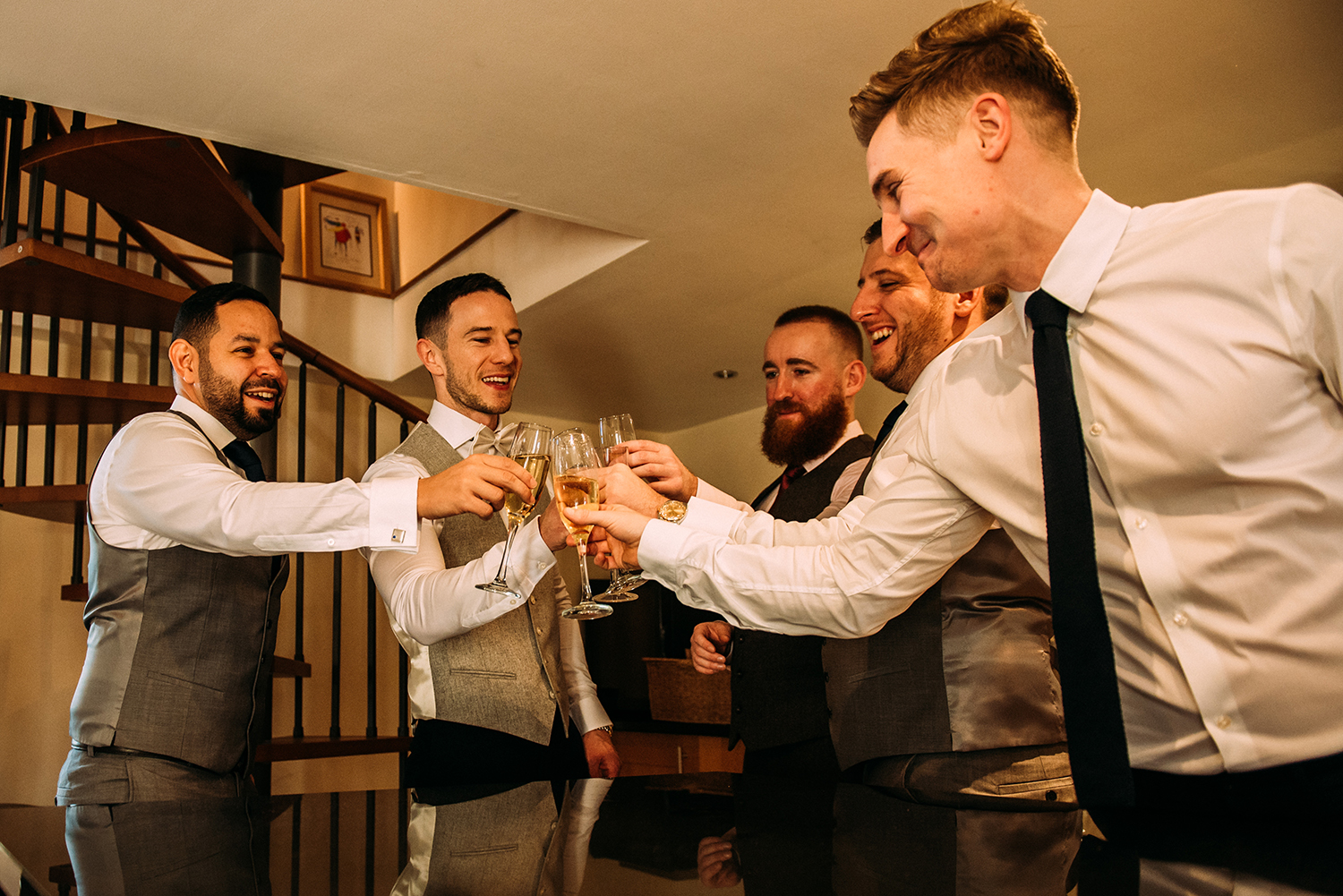 the guys 'cheers' their glasses in the kitchen