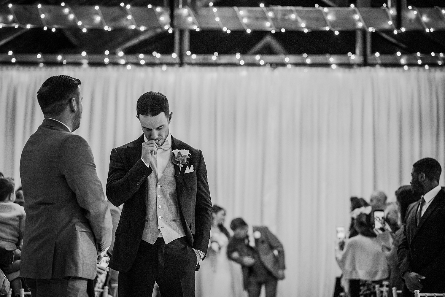 bw photo of nervous groom biting his thumbnail as the bride enters in the background
