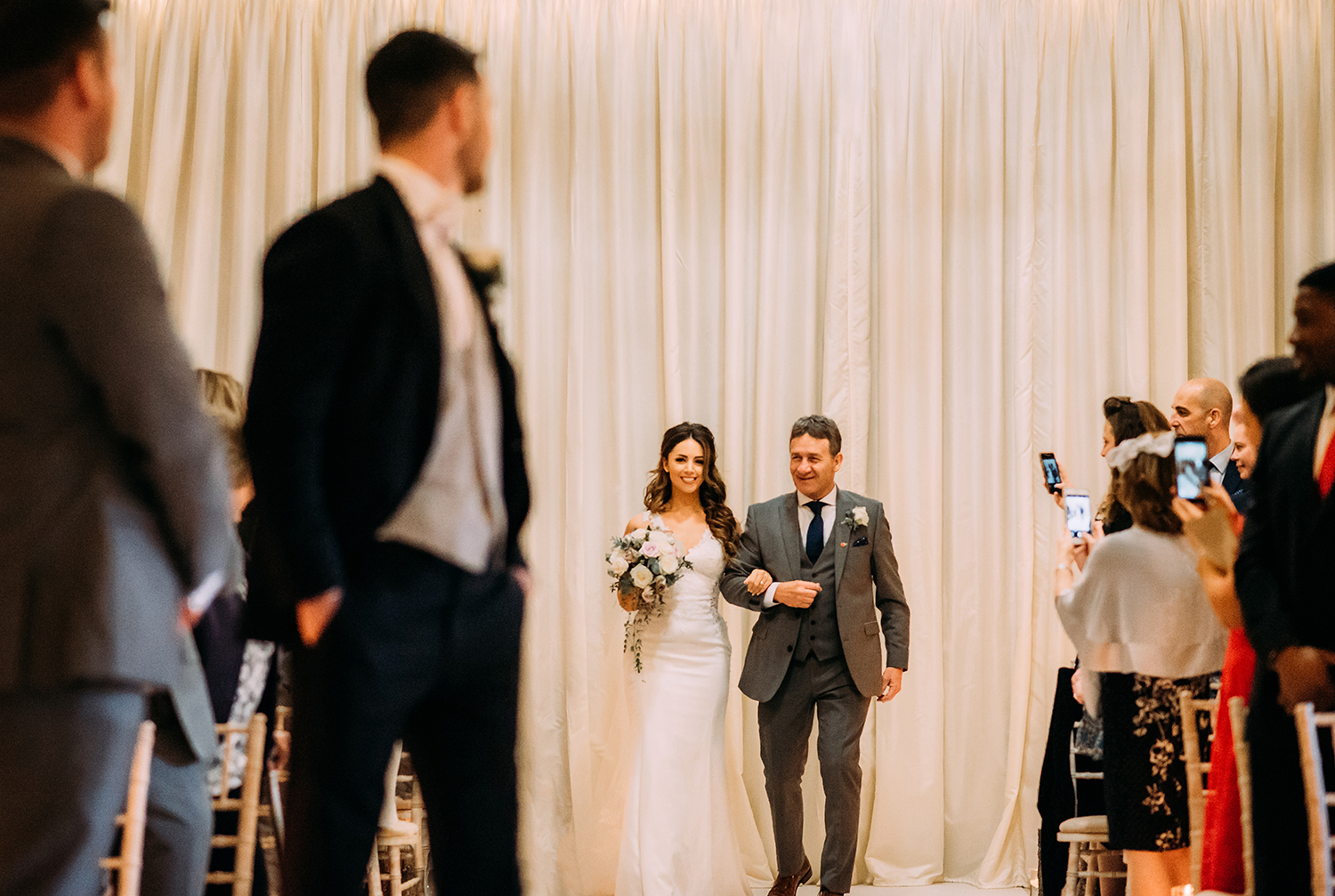 groom looks back at the bride walking down the aisle with her father