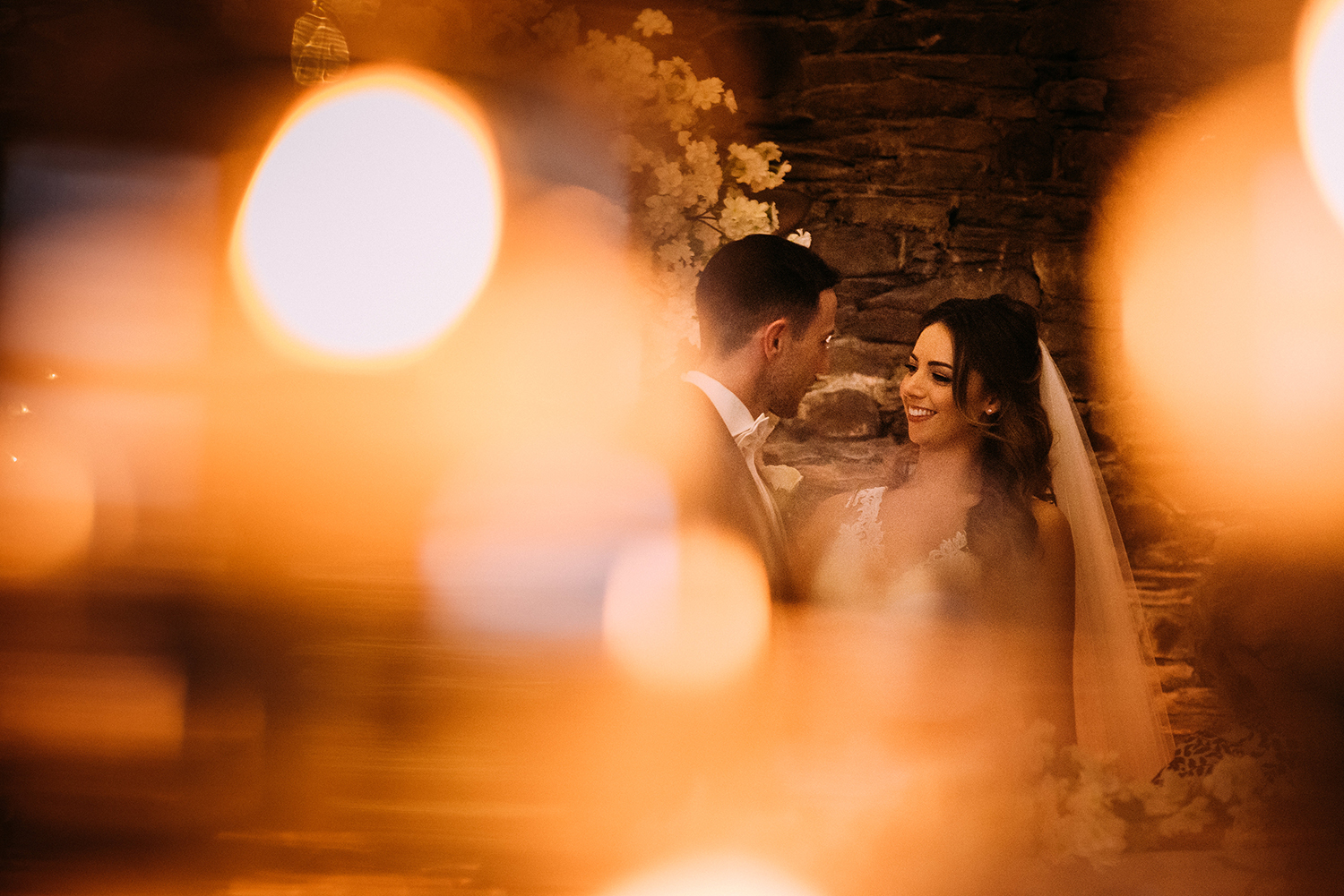 bride smiling at the groom through candle light