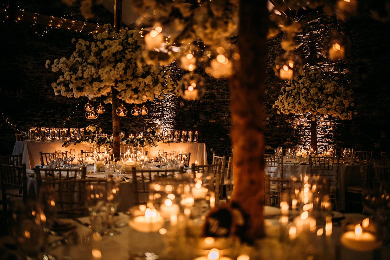 candles hanging from trees on the tables set for the wedding breakfast