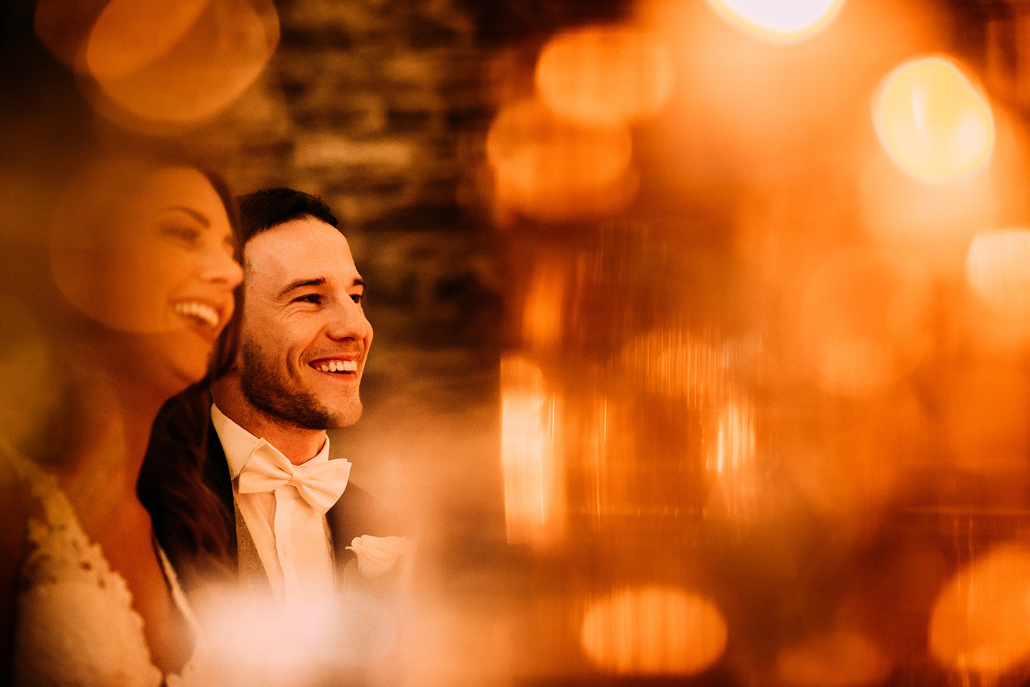 bride and groom laughing through candle light