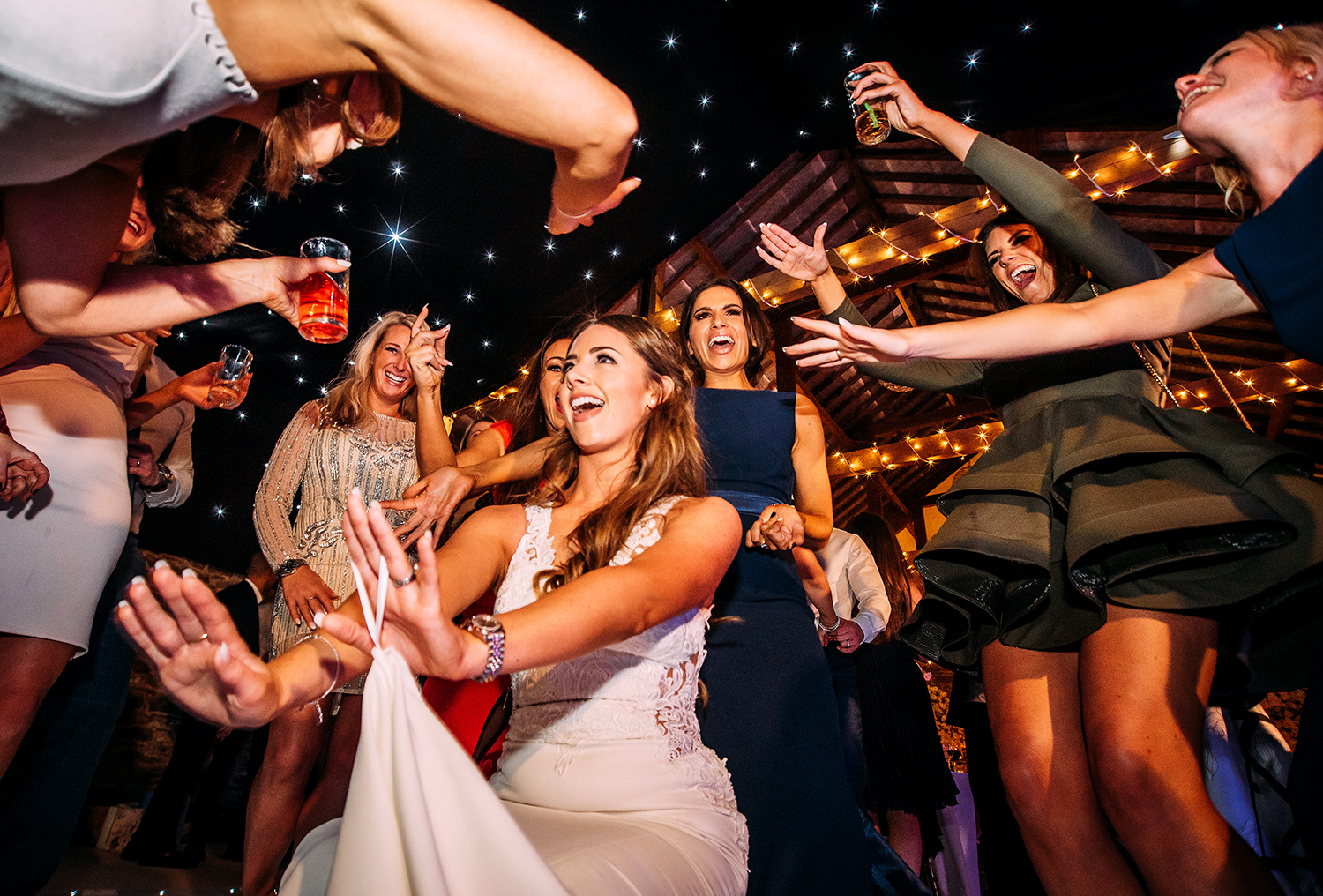 brides friends circle her on the dance floor while they all dance