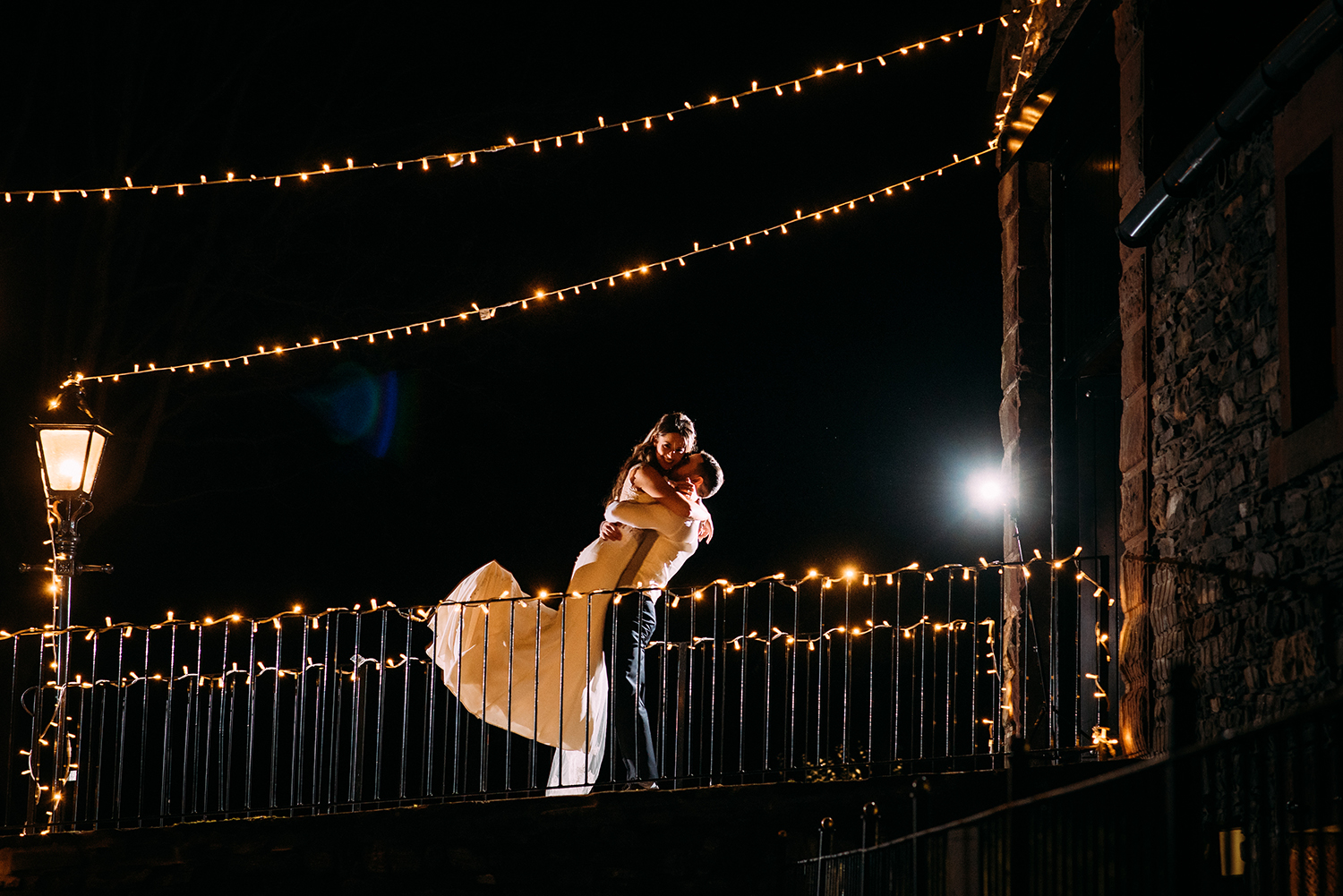 night time shot of the groom lifting the bride in the air