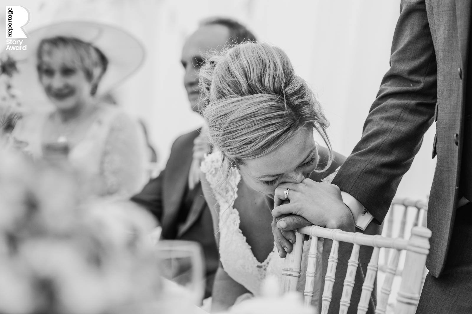 an emotional bride squeezes her husbands hand during his speech. Bw photo