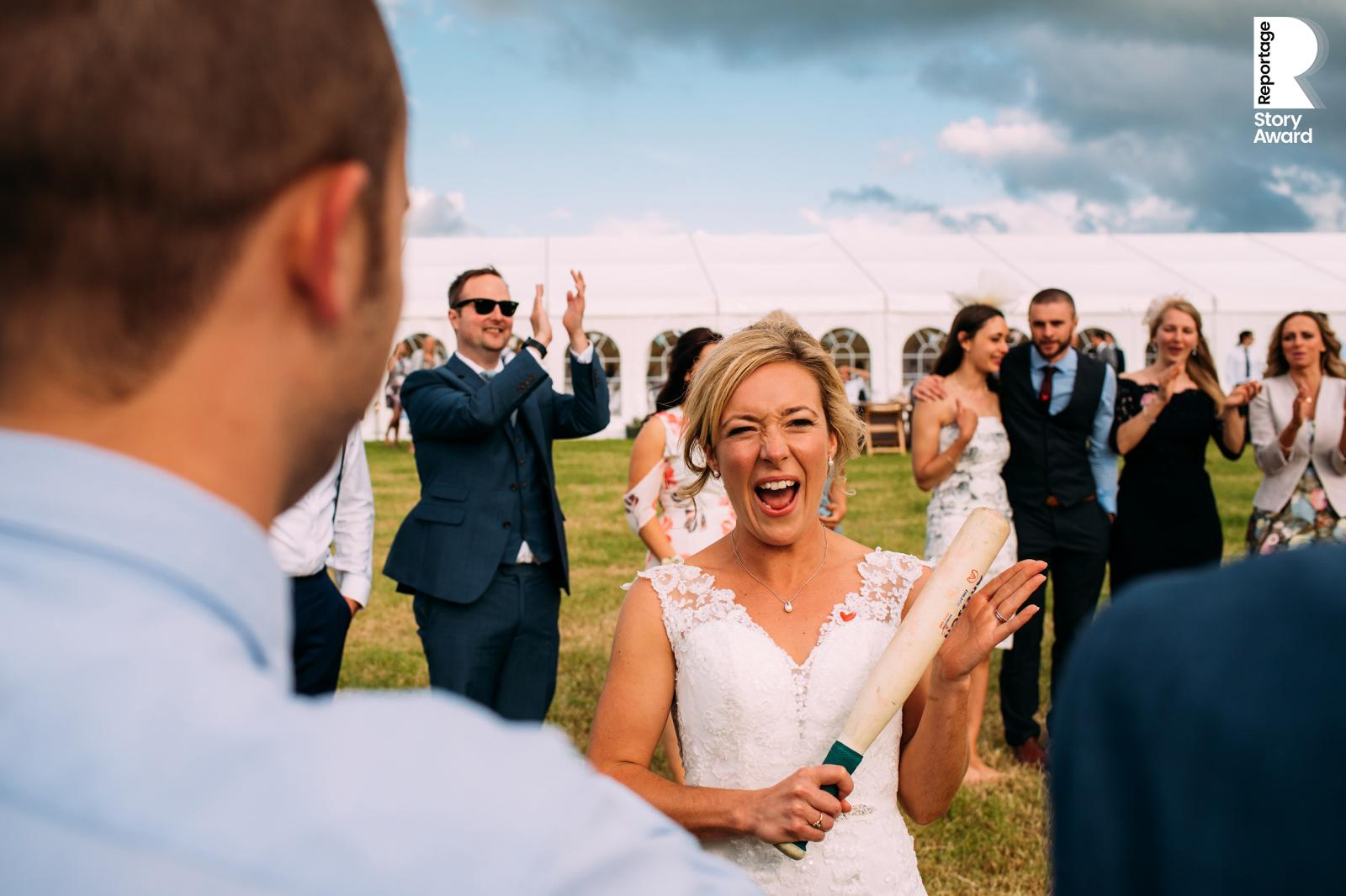 game of rounders. The bride steps up for her turn tapping the bat in her hands