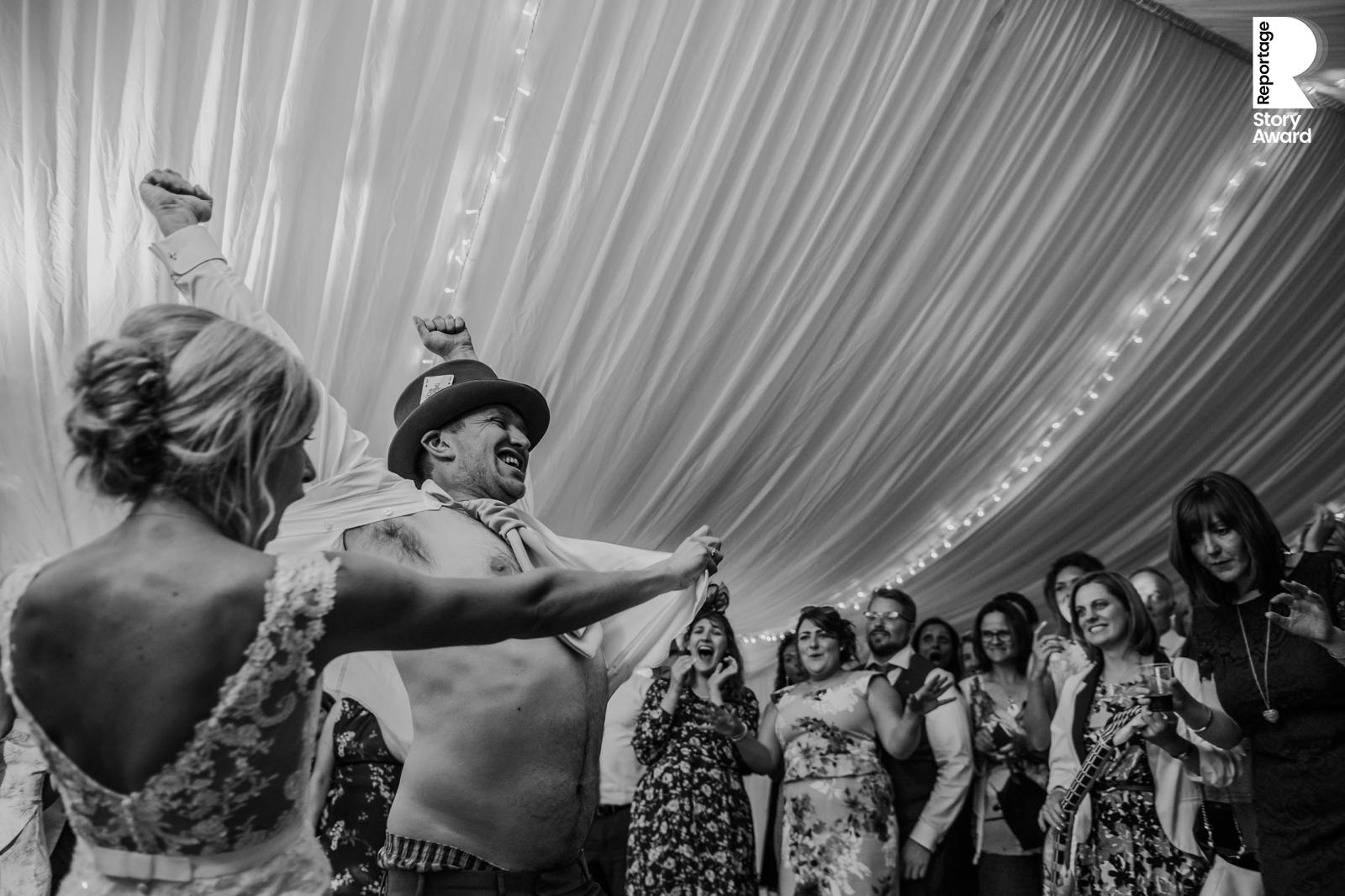 bw photo of the bride opening the grooms shirt on the dance floor while the guests cheer