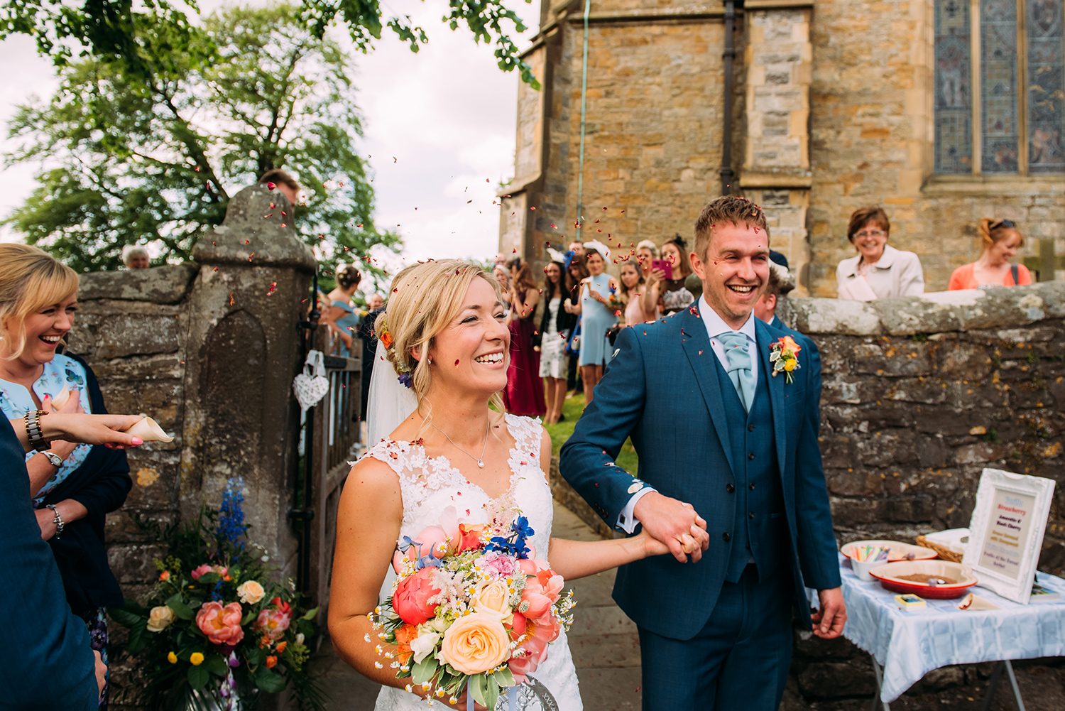 couple walk out of the church grounds with big smiles