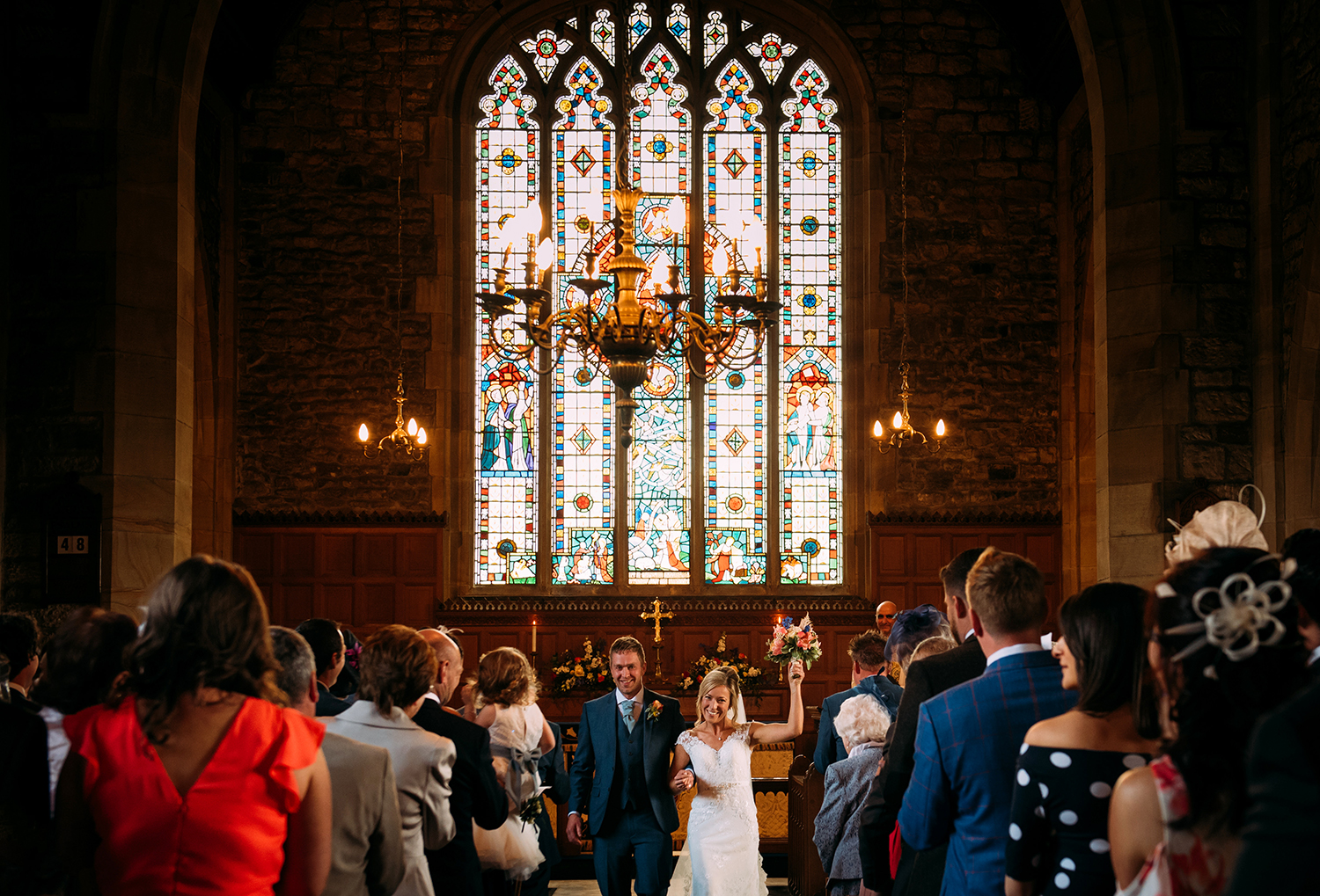 bride holds flowers up and they leave church together