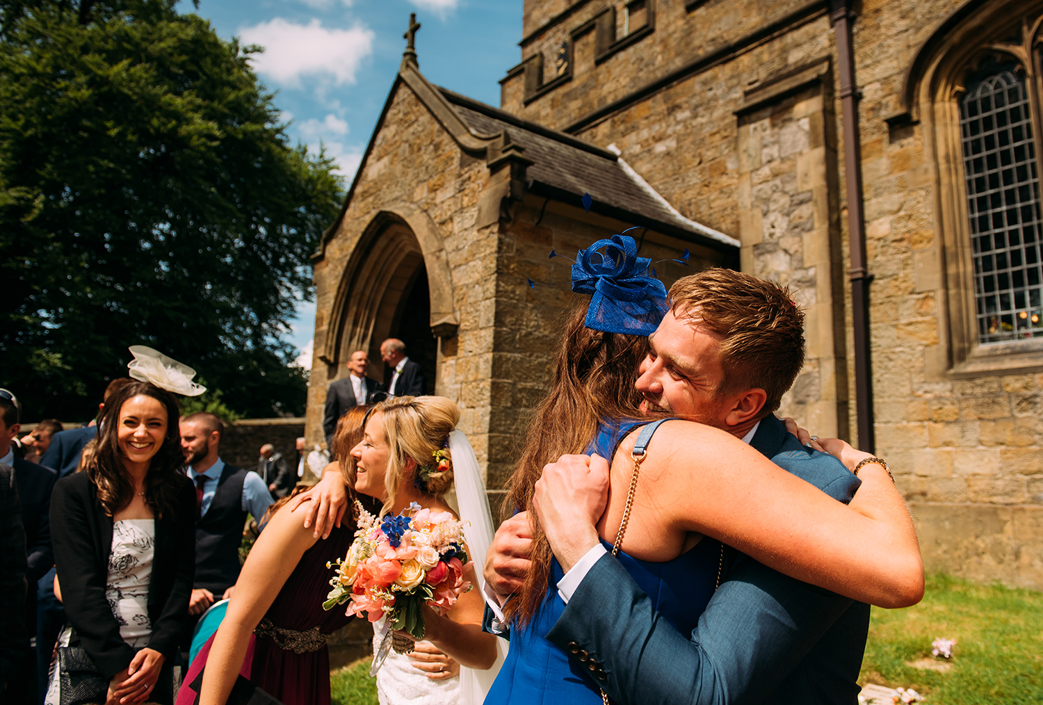 groom hugging a guest outside church