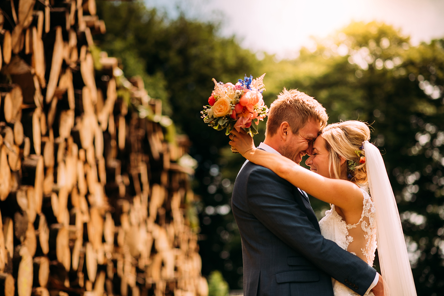 the couple embrace in sun light by a pile of logs